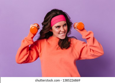 Dark-haired girl smiles and does exercises with dumbbells. Woman in sports bandana and bright sweatshirt poses on purple background