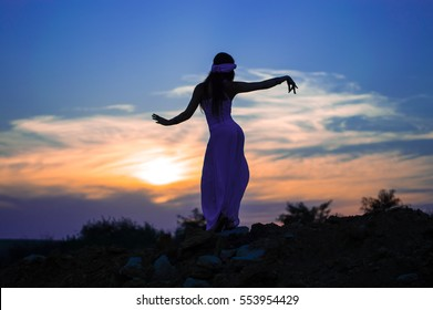 Dark-haired girl in white clothes dancing Oriental dance. Silhouette. Nature. Sunset. Mountainous terrain.