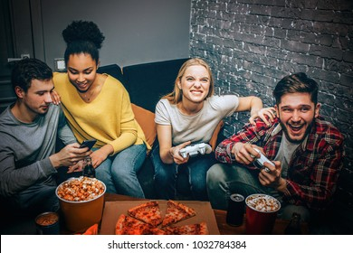 Dark-haired guy and afroamerican girl are looking to the phone with sone interest while the blonde-haired girl and her friend are playing game. The game is veru intensive. Night party