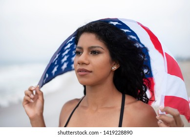 dark-haired Latina woman holds American flag above head at the beach celebrating 4th of July