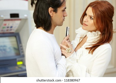 Dark-haired man with credit card in hand and red-haired woman stand face to face, focus on woman