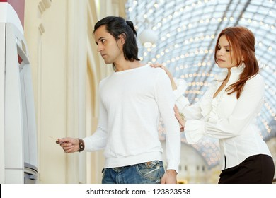 Dark-haired man with credit card and red-haired woman stand near to cash dispenser