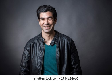 Dark-haired man with green t-shirt and leather jacket, looks smiling isolated on dark background