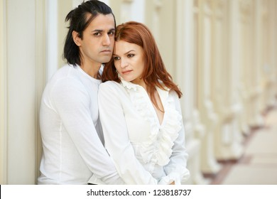 Dark-haired man and red-haired woman stand embraced and  leaned to wall