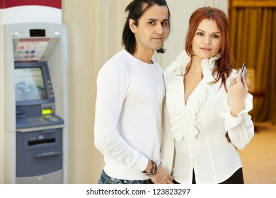 Dark-haired man and red-haired woman stand near to cash dispenser, she holds credit card