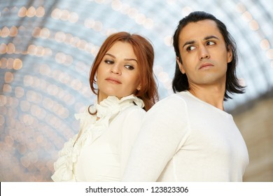 Dark-haired man and red-haired woman stand back to back and looking at each other over their shoulders, focus on man