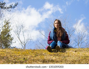 Dark-haired pretty attractive girl in a jacket and blue scarf sits on a sunny day in a park on the grass in spring against the blue bright sky in Lappeenranta, Finland. Vacation period in May, outdoor
