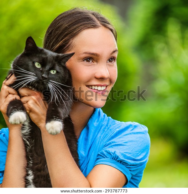 Dark-haired smiling beautiful young woman in blue blouse with black cat, against green of summer park.