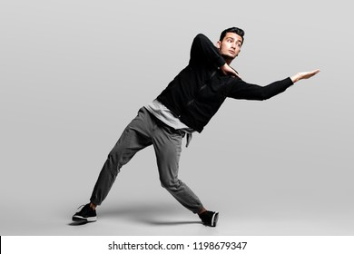 1a4c601a Dark-haired stylish young man wearing a black sweatshirt and gray pants is  dancing street