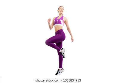 A dark-haired woman coach in a sporty pink short top and gym leggings doing exercise to warm up the legs, alternate knee flexion  on a  white isolated background in studio