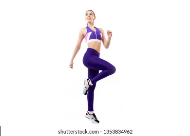 A dark-haired woman coach in a sporty purple  short top and gym leggings doing exercise to warm up the legs, alternate knee flexion  on a  white isolated background in studio