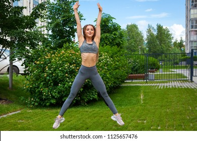 A dark-haired woman coach in a sporty short top and gym leggings does sports exercise and jumps up  on a summer day in a park on a green lawn