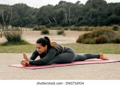 Mujer de cabello oscuro, estirando antes de practicar yoga o pilates, en un parque natural con un fondo de árboles encaramados en el suelo, vestido gris con alfombra rosa
