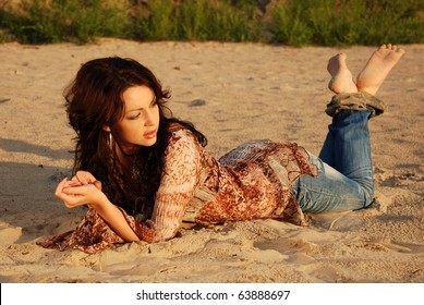 A dark-haired woman lying on the sand