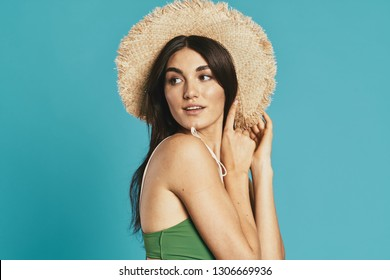 Dark-haired woman in a straw hat in a green bathing suit on a blue background looking to the side