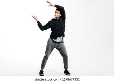 Dark-haired young man wearing a black sweatshirt and gray pants is dancing street dance. He makes stylized movements with his hands