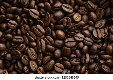 Darkly lit roasted coffee beans, piled together and filling frame to create a background texture in multiple shades of brown and gold.