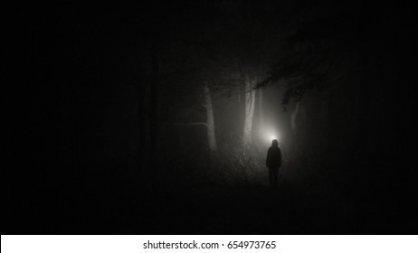 Darkness around a man with a flashlight
