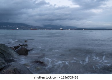 As darkness descends and the lights slowly come on over English Bay after an early winter storm the waves gently lap at the rocky beach while slowly turning the cargo ships with it. Vancouver, BC.