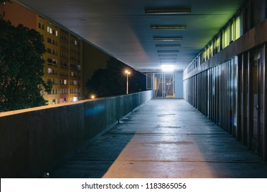 Darkness in an old grunge dirty street in the middle of night with cool glowing thungsten lights and yellow street lamps. Single Point Perspective