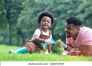 Dark-skinned boy and his father spent time outdoors on summer days, boy learning to plant trees and looking at camera