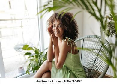 Dunkelhäutige Brunette-Frau in Seidenkleid sitzt auf dem Sessel in weißem Raum mit Pflanzen. Curly Lady in grünem Outfit lächelt.