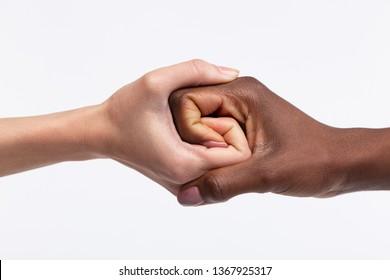 Dark-skinned friend. Women with white skin shaking hand of her dark-skinned friend while respecting equality