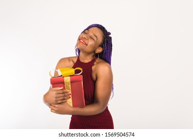 A dark-skinned girl holds a huge red gift with a gold bow in her hands, looks at the camera and smiles. Concept of holiday, New year and Christmas, receiving gifts for Birthday and Valentine's Day.