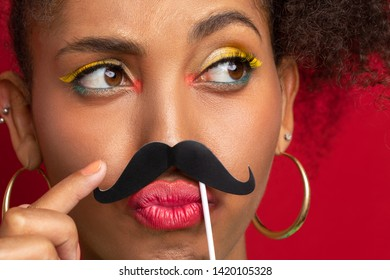a dark-skinned girl jokes with a cardboard mustache in her face. close-up portrait of funny model on red background