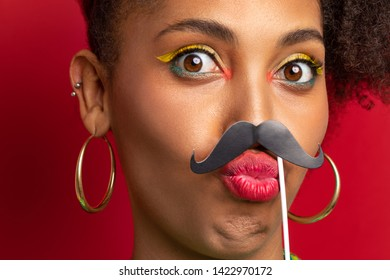 a dark-skinned girl jokes with a cardboard mustache in her face. close-up portrait of funny model on red background. Girl having fun and joking
