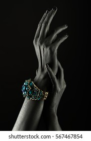 Dark-skinned hand with a gold bracelet on a black background. Beautiful hands. Luxury lifestyle