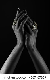 Dark-skinned hand with jewelry on a black background. Hands close up of young woman with black manicure with rings. Luxury lifestyle