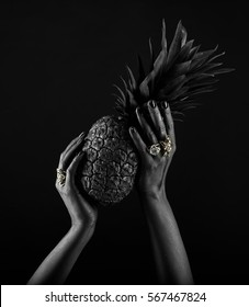 Dark-skinned hand with jewelry on a black background. Beautiful hands with rings on the fingers. Hands holding a pineapple
