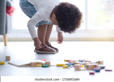 Dark-skinned little boy bent over wearing shoes by himself