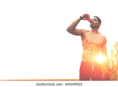 Dark-skinned runner drink water after intensive evening run, athlete refreshing with bottle of water after running workout