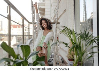 Dark-skinned woman in silk green dress and cardigan sits at swing on balcony. Curly lady listens to music in headphones.