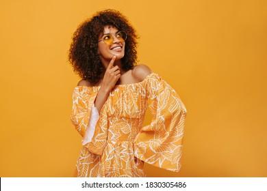 Dunkelhäutige Frau in einer Sonnenbrille, die auf isoliertem Hintergrund lächelt. Pensive Mädchen in Sommerkleidung posiert auf gelbem Hintergrund.