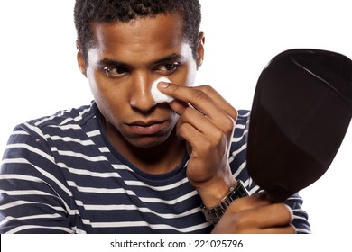 dark-skinned young man cleanse his face with cotton pad