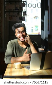 Dark-skinned young man sits in caf by table with laptop, drinks coffee and dreamily looks out the window. Bearded handsome man with dark eyes take few sips of coffee and smile. Cheerful guy with