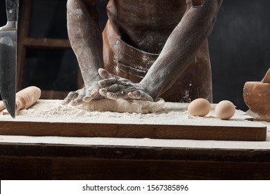 dark-skinned young man standing in a brown leather apron on a nude torso in a dark room and kneading the dough