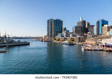 Darling Harbour district area with people on the promenade, boats near the docs and city skyline view. Sydney, Australia. August 30, 2017