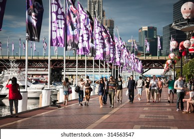 DARLING HARBOUR, SYDNEY, AUSTRALIA - DECEMBER 23, 2014: People leisurely walking on the promenade in the Darling Harbour in sunsetting light during Christmas time