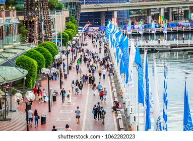 DARLING HARBOUR, SYDNEY, AUSTRALIA - February 10, 2017: People leisurely walking on the promenade in the Darling Harbour in sunsetting ligh