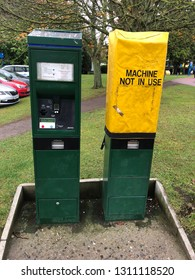 """Darlington, County Durham, UK - Oct 13 2018: Two Parking Machines in Darlington Memorial Hospital Car Park at 12.53pm. There is a bright yellow """"Machine Not In Use"""" Bag covering the right hand machine"""
