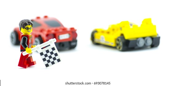 DARLINGTON, ENGLAND - MARCH 4, 2017: Red and Yellow LEGO cars passing the checkered flag, held by a LEGO mini figurine.