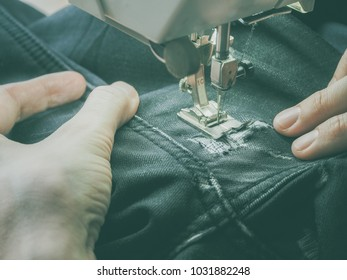 Darning jeans on a sewing machine.