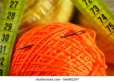Darning needle is put into a ball of yarn, lies next to the measuring centimeter