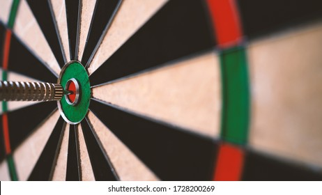 Dart arrow in the center of dartboard bulleye. Close up conceptual image of target and goal. Shallow depth of field.
