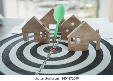 Dart arrow or dartboard hitting on number target center with miniature wooden house models. Success Gold of property mortgage or real estate investment business concept, vintage tone, soft focus