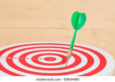 dart arrow and dartboard on wood background